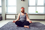 A funny fat bearded man in the headphones does yoga in the room. - 202186772