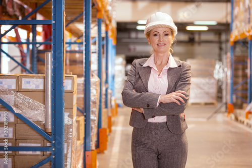 Global commerce. Delighted confident businesswoman looking at you while standing in the warehouse