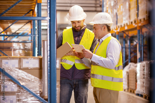 Large scale trade. Delighted nice man holing a box while standing with his colleague in the warehouse