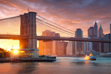 Famous Brooklyn Bridge in New York City with financial district - downtown Manhattan in background. Sightseeing boat on the East River and beautiful sunset over Jane's Carousel. - 202194912
