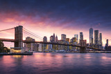 Famous Brooklyn Bridge in New York City with financial district - downtown Manhattan in background. Sightseeing boat on the East River and beautiful sunset over Jane's Carousel. - 202194976