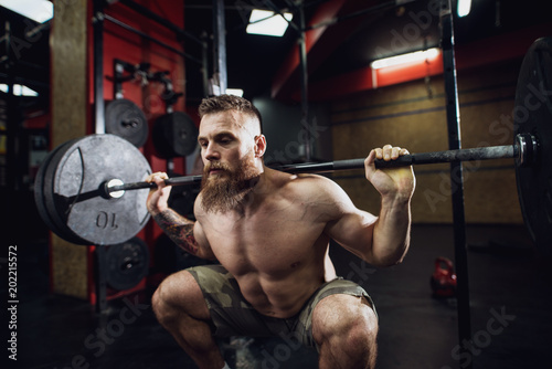 Portrait view of young bearded focused strong muscular fitness man crouching with a heavy barbell behind the neck while doing squats in the gym.