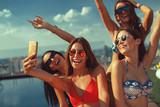 Four young women in a penthouse near the pool doing selfie in a bikini - 202232758