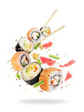 Different fresh sushi rolls with chopsticks frozen in the air on white background - 202240170