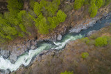 Mountain river flowing in a canyon, bird view, perspective from above, aerial drone shot.