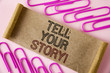 Handwriting text writing Tell Your Story Motivational Call. Concept meaning Share your experience motivate world written on Folded Cardboard paper piece on plain background within Paper Clips.