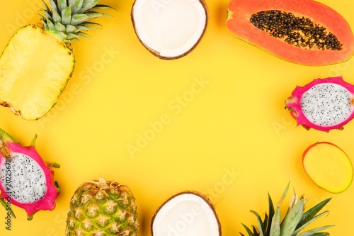 Tropical fruit frame with pineapple, dragon fruit, papaya, coconut and mango on a bright yellow background - 202256718