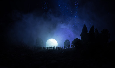 Silhouette of a large crowd of people in forest at night watching at rising big full Moon. Decorated background with night sky with stars, moon and space elements. Selective focus.