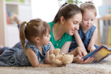 young mom and her children daughters lying on the floor and reading book