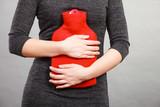 Girl having stomach ache, holding hot water bottle