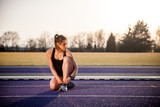 Fitness woman preparing shoes on stadium running track during sunset
