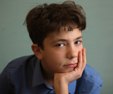 kind teenager boy close up portrait on blue wall background - 202312368