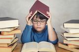niño triste y pensativo con libros sobre una mesa