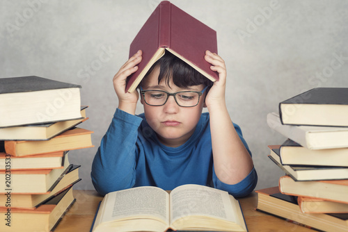 niño triste y pensativo con libros sobre una mesa © esthermm