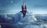 Geschäftsmann sitzt auf Eisberg im Meer - 202324168