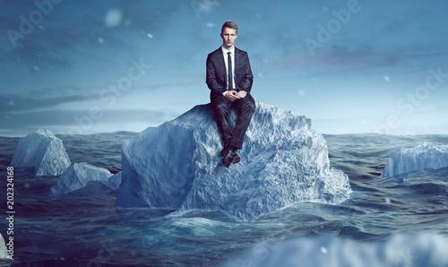canvas print picture Geschäftsmann sitzt auf Eisberg im Meer