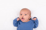 Cute eurasian newborn baby boy wearing a blue infant bodysuit on white sheet and looking at the camera, with copy space - 202331335