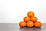 Mandarynki leżące na blacie. Piramida ułożona z mandarynek. Owoce cytrusowe na białym tle.