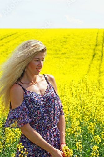 Plexiglas Geel Blonde peasant girl in floral print dress on the yellow blossoming rapeseed field