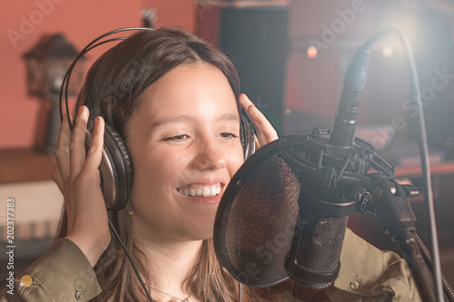 Fototapeta Girl singing with a microphone and headphones