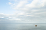 Seascape. Lonely boat on a quiet sea surface - 202389729