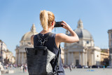 Female tourist with a fashinable vintage hipster backpack taking photo oof Piazza del Popolo, People's Square, in Rome, Italy by her mobile phone. - 202399955