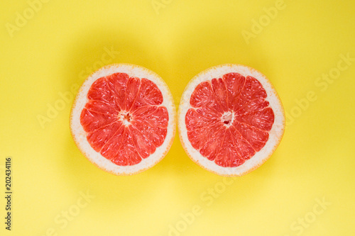 Grapefruit cut in half on a yellow background