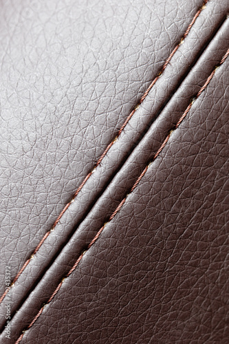 Stitch thread on brown leather material as background