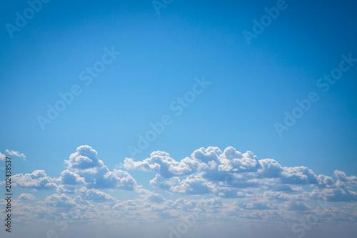 white cumulus clouds against blue sky. background