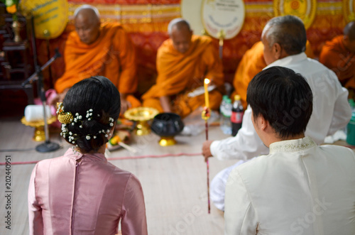 Monks are praying to bless bride and groom in Thai wedding ceremony.