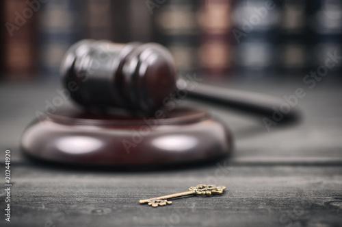 Judge Gavel andold vintage key on a black wooden background.
