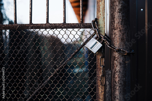 Gates with mesh on lock in iron fence. Metal gate with grid is fortified with diagonal reinforcement. Background image of steel rough gate with lock on chain.