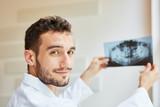 Zahnarzt hält Röntgenbild von Gebiss