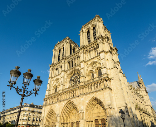 View of the facade and bell towers of Notre-Dame de Paris cathedral, showing the three portals and the rose window in the warm light of the setting sun, with a vintage street light in the foreground.