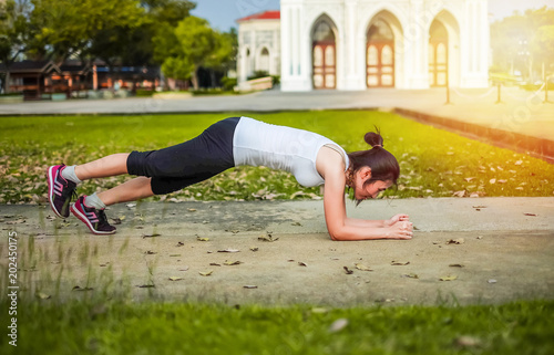 Asia beautiful woman exercising in the green garden.yoga and meditation concept.