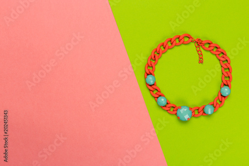 Bijou necklace on a bright bicolor background, top view