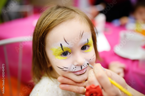 Face painting for cute little girl during kids birthday party
