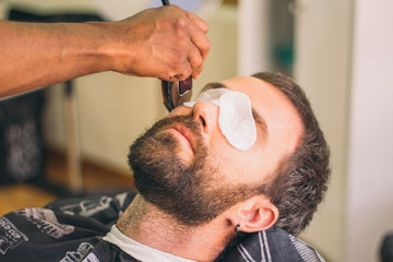 Close up view of man with eye protectors at barbershop. Barber cutting the beard with the trimmer.