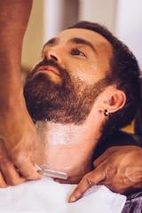 Barber shaves beard of young man at barbershop. Closeup view.