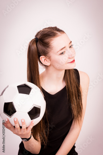 The girl in the dress with the ball for the game of football.