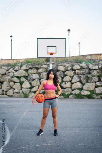 Fotobehang Basketbal Confident female basket player. Young sportswoman at urban basketball court. Urban sport and healthy lifestyle.
