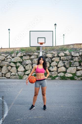 Plexiglas Basketbal Confident female basket player. Young sportswoman at urban basketball court. Urban sport and healthy lifestyle.