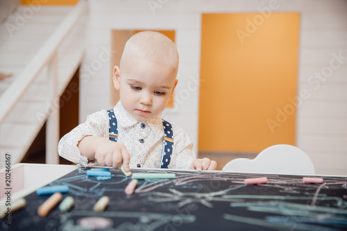 Boy child is drawn with chalk on blackboard with his hands, concept for preparing school, and developing motor skills.