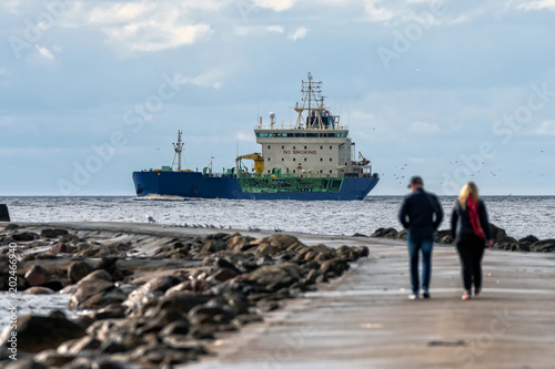 Mole with people in the cloudy evening and in the background sea with cargo ship