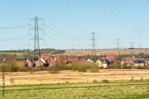 Houses of an English village with overhead power cable lines seen from outside field in early Spring - environmental background - 3