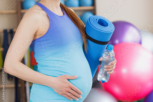 Pregnant sporty woman with a mat for yoga in the hand