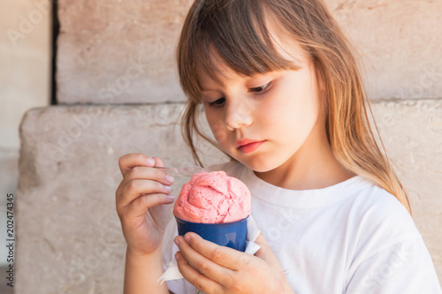 Little blond European girl eats pink ice cream