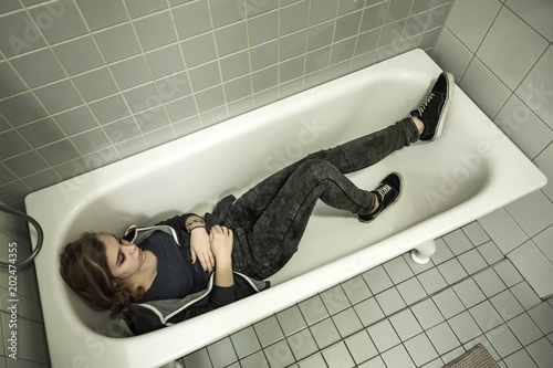 Teenage girl laying in empty shower bath