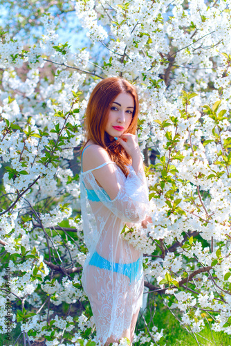 Young girl in the blossom of trees in a romantic transparent lace bohemian dress. The concept of romance and purity