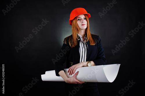 Engineer woman in orange protect helmet with construction paper projekt.